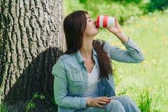 女孩用咖啡在公园 免版税库存图片