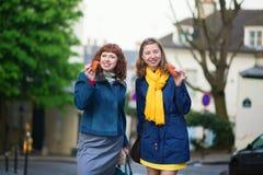 女孩用在一条巴黎人街道上的新月形面包 库存图片