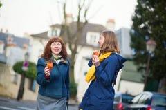 女孩用在一条巴黎人街道上的新月形面包 库存照片