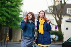 女孩用在一条巴黎人街道上的新月形面包 免版税库存照片