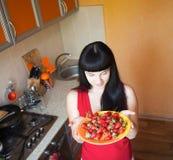 女孩用在厨房的草莓 免版税库存照片
