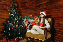 女孩用在圣诞树附近的糖果 库存照片