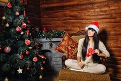 女孩用在圣诞树附近的糖果 库存图片