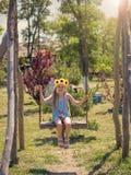 女孩用在她的头的向日葵在摇摆摇摆在村庄在夏日 免版税库存照片