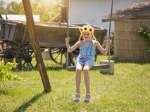 女孩用在她的头的向日葵在葡萄酒摇摆摇摆在村庄在夏日 免版税库存照片