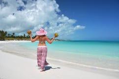 女孩用在海滩的椰子 库存图片