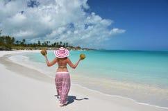 女孩用在海滩的椰子 免版税库存照片