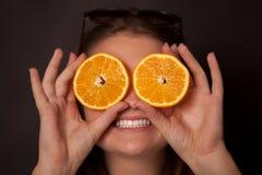 女孩用在眼睛的桔子 库存图片