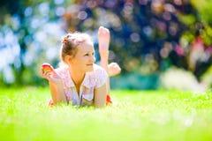 女孩用在绿草的一个苹果 库存图片