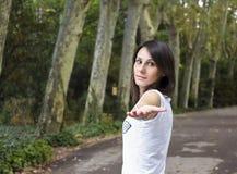 女孩用在美丽forrest的延长的手 免版税库存照片