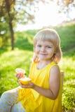 女孩用在草坪的柠檬 免版税图库摄影