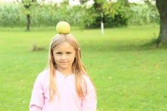 女孩用在头的苹果 库存照片