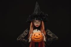 女孩用在黑背景的万圣夜南瓜 免版税图库摄影