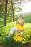 女孩用在绿色草坪的果子 库存照片