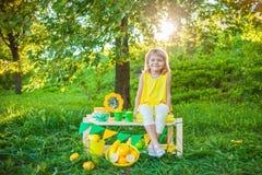 女孩用在绿色草坪的果子 免版税图库摄影