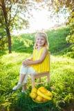 女孩用在绿色草坪的果子 免版税库存照片