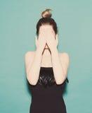 女孩用她的手盖她的面孔 在绿色背景的一件黑礼服在演播室 概念 华美的纵向妇女 库存照片