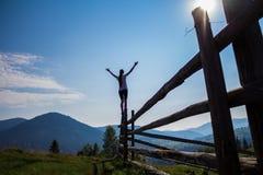 女孩用手在山顶部 免版税库存照片