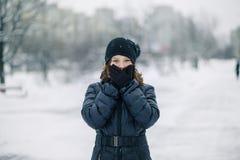女孩用手套盖了嘴 女孩做了一个姿态,沈默 孩子在街道上的学校以后走在降雪 免版税图库摄影