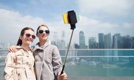 女孩用智能手机selfie棍子在新加坡 库存照片