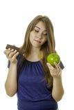 女孩用果仁巧克力和苹果 免版税库存图片