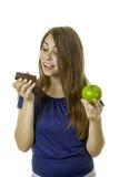 女孩用果仁巧克力和苹果 免版税图库摄影