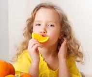 女孩用桔子在家 免版税库存图片