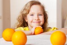 女孩用桔子在家 库存照片