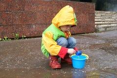 女孩用水使用由桶和铁锹 库存照片