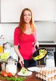 女孩用煮熟的煎蛋卷在家庭厨房里 免版税库存图片