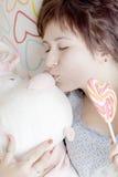 女孩用甜糖果亲吻长毛绒兔子 免版税库存图片
