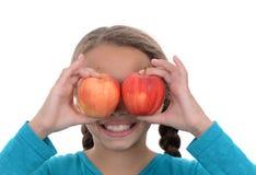 女孩用盖她的眼睛的苹果 库存照片