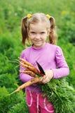 女孩用红萝卜 图库摄影