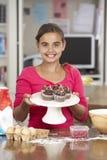 女孩用自创杯形蛋糕在厨房里 免版税库存照片