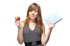 女孩用苹果和书 免版税图库摄影