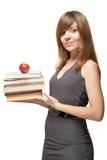 女孩用苹果和栈书 免版税库存照片