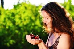 女孩用草莓在手上 免版税库存图片