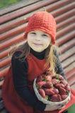 女孩用草莓 有一个红色帽子的女孩 免版税库存图片