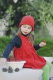 女孩用草莓 有一个红色帽子的女孩 免版税库存照片