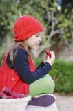 女孩用草莓 有一个红色strawberrries帽子的女孩 免版税库存图片