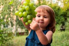 女孩用葡萄 免版税库存照片