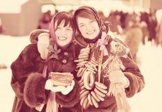 女孩用薄煎饼和圆的脆煎肉片在Shrovetide期间 图库摄影