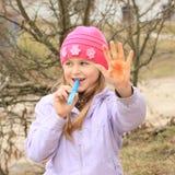 女孩用被绘的手 免版税库存图片