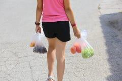 女孩用购物在袋子的水果和蔬菜 图库摄影