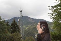 女孩用途智能手机,有卫星盘在电信塔、电信和发展的电信网络的 库存照片