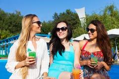 女孩用饮料在夏天在水池附近集会 库存照片