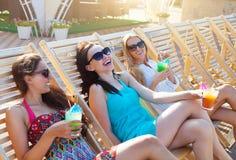 女孩用饮料在夏天在水池附近集会 免版税库存照片