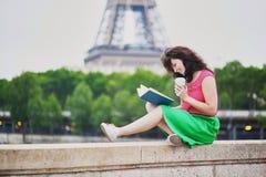 女孩用去的咖啡读书在埃佛尔铁塔附近 库存图片