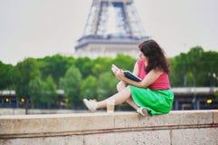 女孩用去的咖啡读书在埃佛尔铁塔附近 免版税库存照片