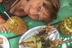 女孩用pina colada菠萝和桌与龙虾 旅行的概念 图库摄影